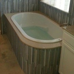 Oval Drop-in tub installed in the corner, glass tile